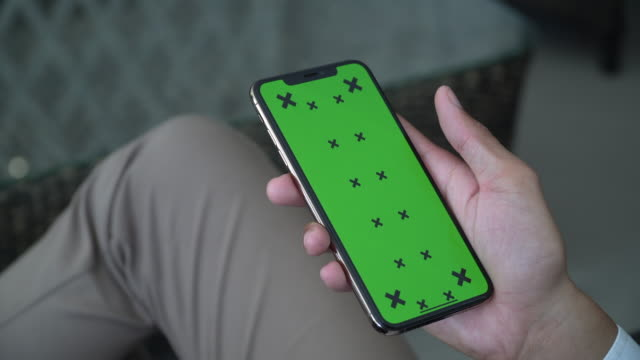vidéos et rushes de nouvel écran clé chroma de téléphone portable sur la main de l'homme d'affaires - fond vert