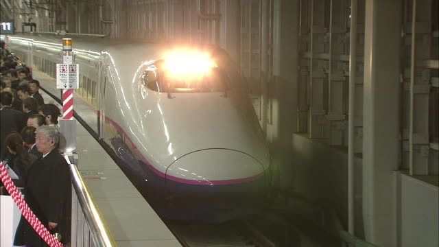 A new model Hayate Number 12 high speed train approaches the Aomori Station platform