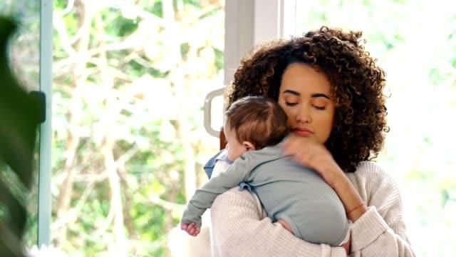 vidéos et rushes de la nouvelle maman rote son petit garçon après une alimentation - vêtement de bébé