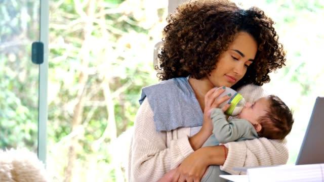 vídeos y material grabado en eventos de stock de nueva mamá cuida de su recién nacido mientras teletrabajo - son