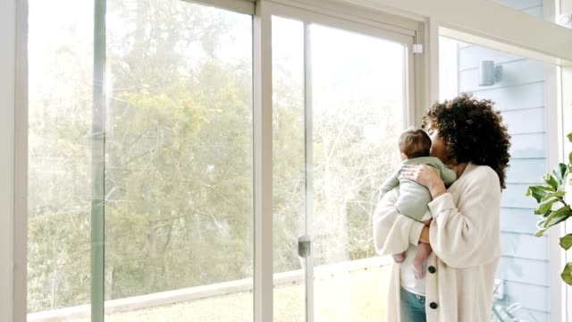 new mom looks through window while holding infant son - burping stock videos & royalty-free footage