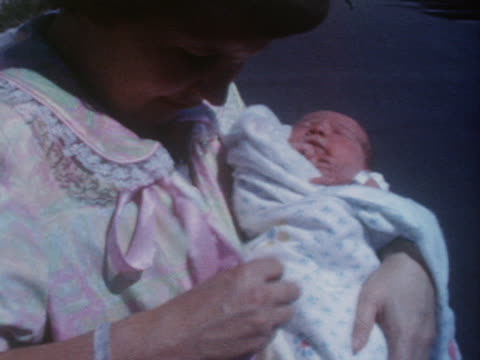 a new mother holds her swaddled infant; new parents pose with their infant. - image stock videos & royalty-free footage