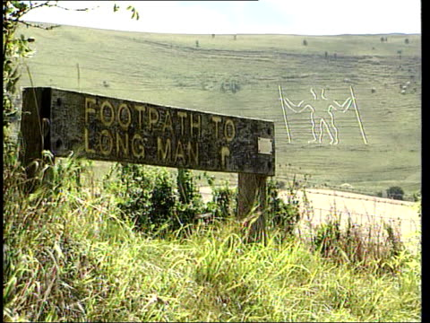 New national parks LIB South Downs MS Sign 'Footpath to Long Man' as Long Man of Wilmington on hillside behind GV Long Man figure on hillside...