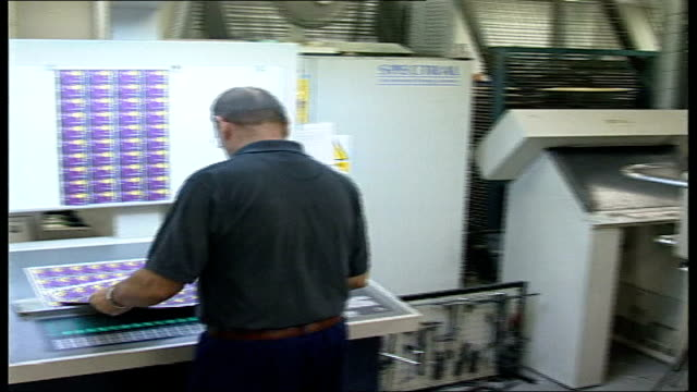 New 'Nectar' loyalty card introduced Nectar loyalty cards printed off on machine PULL Worker pulling sheet of cards from machine Sheet laid against...