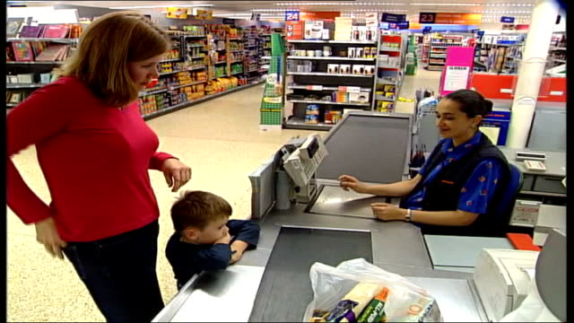vídeos de stock e filmes b-roll de new 'nectar' loyalty card introduced woman handing over nectar loyalty card at checkin counter of sainsbury's store ms card swiped by cashier ltn - sainsburys