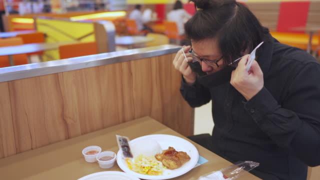 vídeos de stock e filmes b-roll de 4k new normal eating. asian man taking off face mask before having food for lunch in restaurant - povo tailandês