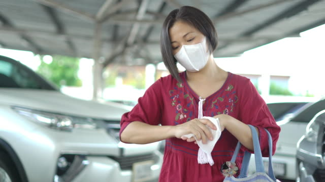new normal life after covid-19, asian woman wiping hands with tissue paper after shopping in the supermarket at parking lot. - tissue paper stock videos & royalty-free footage