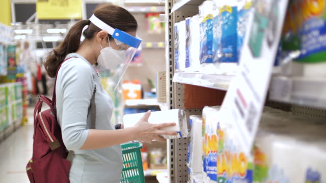 new normal life after covid-19 virus, asian woman wearing face mask and face shield shopping in supermarket - convenience stock videos & royalty-free footage