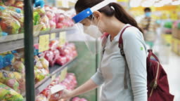 New normal life after COVID-19 Virus, Asian woman wearing Face mask and face shield shopping in Supermarket