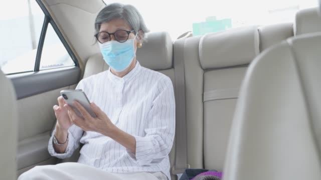 neue normale beifahrerin, asiatische alte frau tragen maske im auto und verwenden smartphone - taxi stock-videos und b-roll-filmmaterial