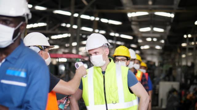 vídeos de stock e filmes b-roll de new normal queue line of factory workers checking temperature - pessoas em fila