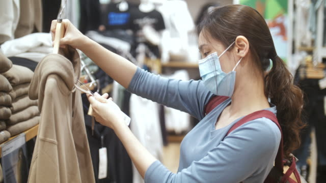 new normal shopping, asian woman shopping in clothing store with face mask - retail stock videos & royalty-free footage