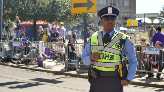 A New Orleans Police Department officer controls the intersection St Charles Avenue at Howard Avenue on Lee Circle before the Krewe of Okeanos parade