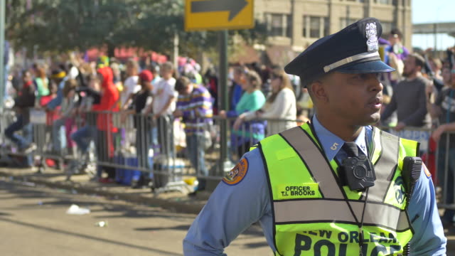 A New Orleans Police Department officer controls the intersection St Charles Avenue at Howard Avenue on Lee Circle during the Krewe of Okeanos parade