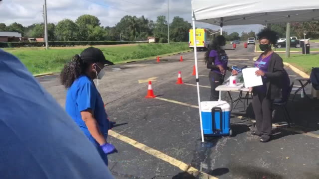 stockvideo's en b-roll-footage met new orleans, u.s. - medic in protective suit collecting nasal sample from police officer at university of holly cross on thursday, september 24, 2020. - testkit