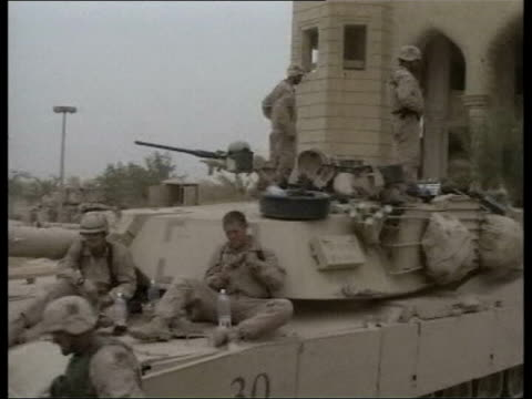 vidéos et rushes de new pictures of saddam hussein broadcast ms us army m1a1 abrams tanks track marines sitting in garden tls us marines laying down in garden - irak