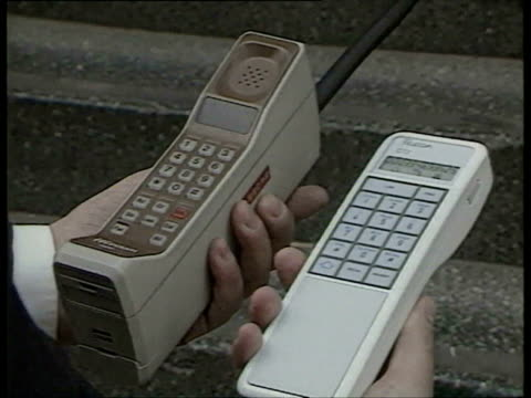 1988 film montage new portable phone next to chunky older model/ ms zi woman making phone call/ hs ws mall/ cu zo phonepoint sign in mall/ ws zi phonepoint sign on train station/ london, england/ audio  - 1980~1989年点の映像素材/bロール