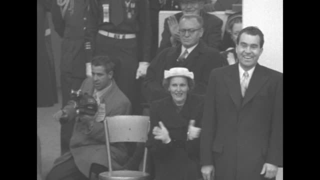 new pres. dwight eisenhower standing on reviewing stand watching parade, former president herbert hoover sitting to his left next to eisenhower's... - 大統領就任式点の映像素材/bロール