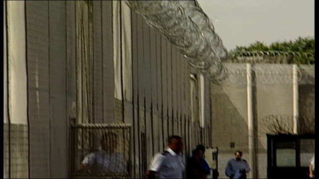 new research reveals high rate of re-offending by released prisoners; date unknown location unknown: ext prison wall with barbed wire tilt down... - wire mesh fence stock videos & royalty-free footage