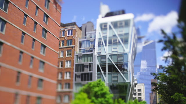 new residential buildings stand along the high line park behind the fresh green trees in spring season at new york city ny usa on may 15 2019. - chelsea new york stock videos & royalty-free footage