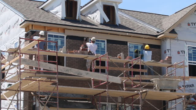 vidéos et rushes de new residential construction, three bricklayers work on exterior of home - classe ouvrière