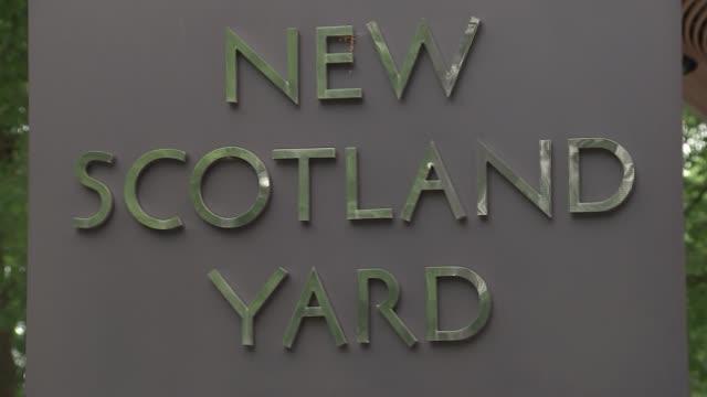 london new scotland yard ext news scotland yard revolving sign / police officer chatting in doorway / gv building / marble bust of sir robert peel - ニュースコットランドヤード点の映像素材/bロール