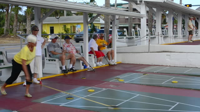 New Smyrna Beach Florida senior retired couples playing shuffleboard in game competition in town on Flaglaer Street