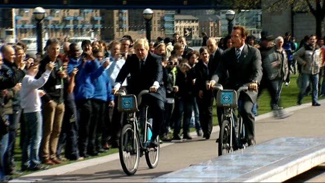 new sponsor wanted for london's bicycle hire scheme; t31031111 / tx 31.3.2011 johnson and arnold schwarzenegger riding hire bikes past crowds johnson... - arnold schwarzenegger stock-videos und b-roll-filmmaterial