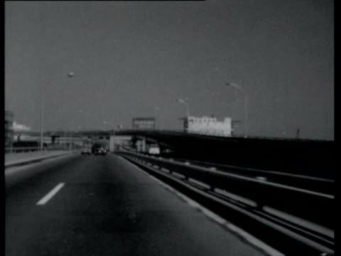 vídeos de stock e filmes b-roll de new super highway alongside monorail which goes from airport to city center / tracking shot along new highway heading towards olympic village views... - 1964