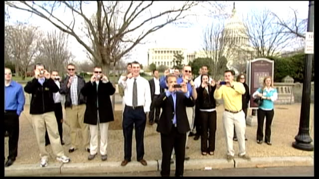 washington ext bystanders at side of road taking photographs presidential limousine passing as barack obama waves through windiow - limousine luxuswagen stock-videos und b-roll-filmmaterial