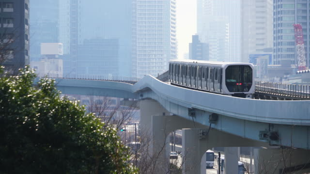 vidéos et rushes de new transit yurikamome (tokyo waterfront new transit waterfront line) runs on elevated railway among the high-rise office buildings and residential buildings around the shiodome district in minato ward tokyo japan on jan. 18 2018. - train de banlieue