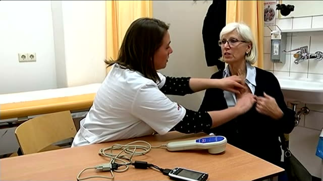 New treatment for arthritis sufferers NETHERLANDS Amsterdam INT Marie Vrind along corridor and into room with doctor Vrind having chest examined and...