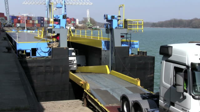 ms new truck loading in container ship wã¶rth harbour with rhine river / wã¶rth, rhineland palatinate, germany - nave video stock e b–roll
