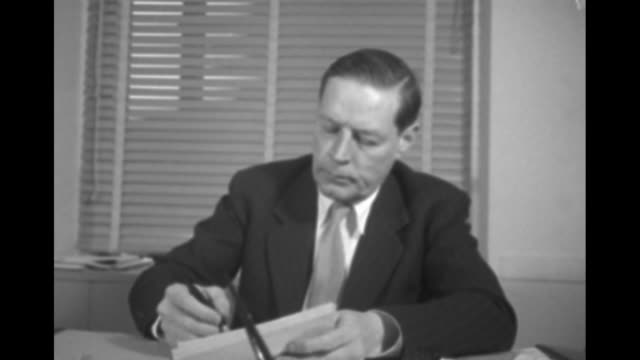 New US Ambassador to the USSR Charles Bohlen sitting at desk in office reading document woman steps up to him and hands him document Bohlen signs and...