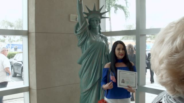 New US citizens take pictures with a replica of the Statue of Liberty after taking part in a US Citizenship Immigration Services naturalization...