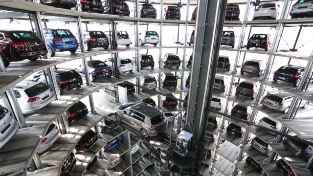 new volkswagen ag vw automobiles sit in storage bays inside one of the glass delivery towers at the vw factory in wolfsburg germany on friday april... - wolfsburg lower saxony stock videos and b-roll footage