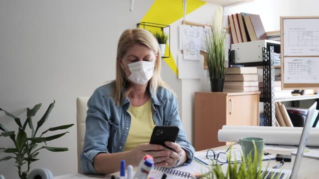 新しい作業環境 - ラップトップで作業フェイスマスクを持つ成熟した女性 - フェイスパック点の映像素材/bロール