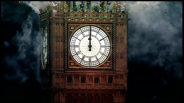 celebrations in london and around the world; england: london: ext / night big ben clock face as striking midnight as fireworks launched from big ben... - midnight stock videos & royalty-free footage