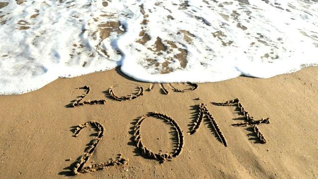 vidéos et rushes de nouvelle année, vieille 2017 année 2016 écrit dans le sable - gomme