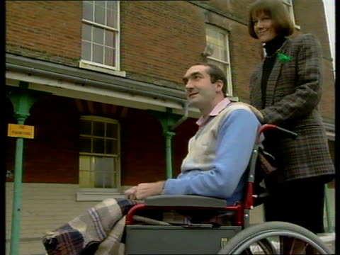new year honours list announced; england: essex: colchester general hospital: ext side sgt andrew mudd pushed along in wheelchair by wife margaret... - the dominion theatre stock videos & royalty-free footage