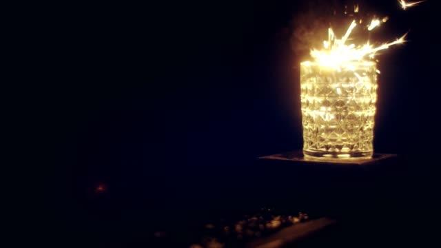 vidéos et rushes de célébration du réveillon du nouvel an. sparklers alluant dans un bocal - verre translucide