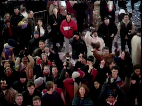 vídeos de stock e filmes b-roll de new year's eve in times square crowd cheering and waving - 1999