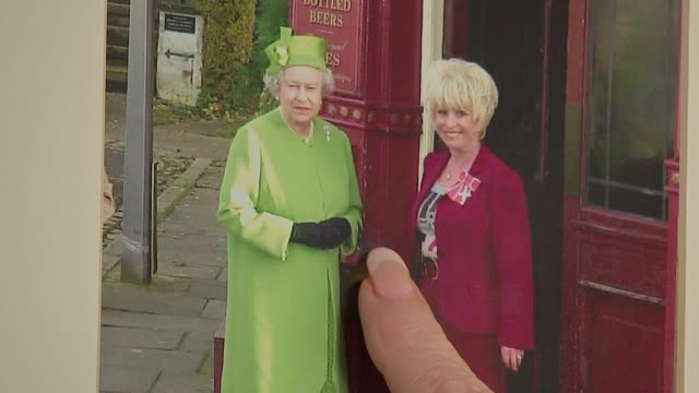 vídeos de stock e filmes b-roll de new year's honours list 2016 barbara windsor interview framed photograph on wall of windsor meeting queen on set of eastenders and talking about... - eastenders