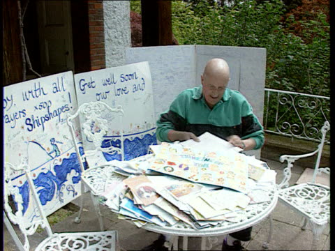 new years honours list; ext roy castle sitting at garden table with 'get well soon' cards cms his hands as shuffling papers tilt up castle reading... - roy castle点の映像素材/bロール