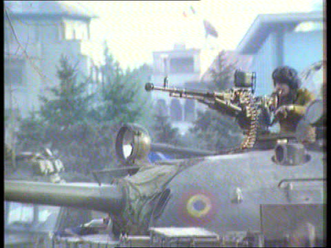 new years honours list; romania: bucharest: cms side top of tank with man manning gun as firing heard sof lms side tank moving round by tv station... - romania点の映像素材/bロール