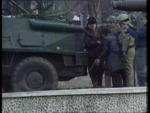 vídeos de stock, filmes e b-roll de bucharest lms side civilians one carrying blue white and red flag with hole in centre bv soldiers lying down in street with guns at ready with... - 1992