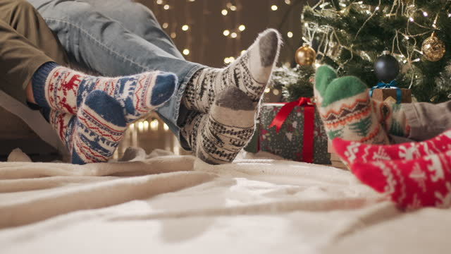 new year's party four people in christmas socks move their feet while sitting on the sofa and floor - sock stock videos & royalty-free footage