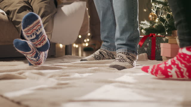 new year's party of several friends in socks with a christmas pattern dancing near the christmas tree - sock stock videos & royalty-free footage