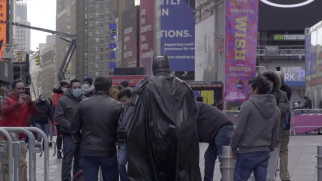 new york 2021 tourists with batman in times square take selfies billboards - ヒーロー点の映像素材/bロール