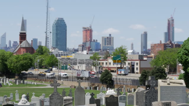 new york calvary cemetery,traffic, and manhattan buildings - tombstone stock videos and b-roll footage